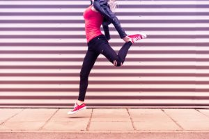 s_young-happy-woman-jumping-in-front-of-metal-wall-2-picjumbo-com
